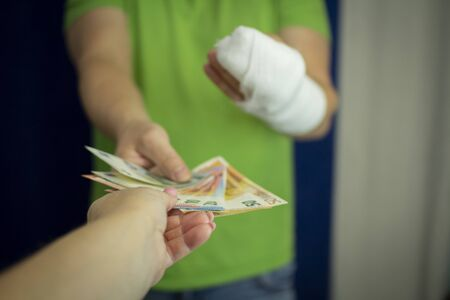 A man with an arm in a cast keeps money from the cost and expense of emergency medical care in a hospital . Paid medicine..Man's hand in bandages after surgery.
