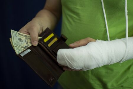 A man with an arm in a cast counted out money from the cost and expenses of emergency medical care at the hospital . Paid medicine..Man's hand in bandages after surgery.