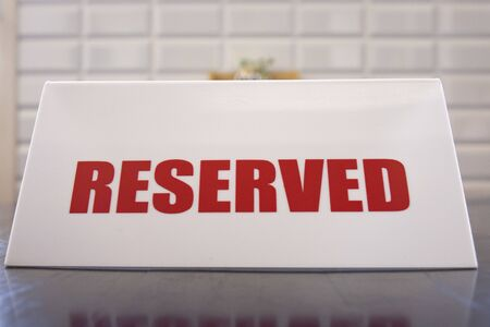 A sign that says reserved on a table in a restaurant or cafe, selective focus. Standard-Bild
