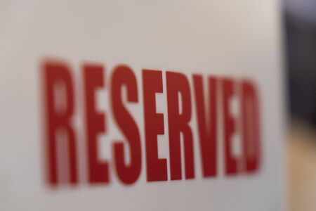 A sign that says reserved on a table in a restaurant or cafe, selective focus.