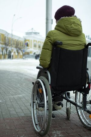 A disabled person in a wheelchair moves around the city in winter.