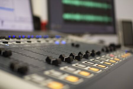 Professional audio mixing console with faders and adjustment knobs. Radio and television broadcasting