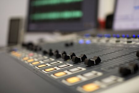 Professional audio mixing console with faders and adjustment knobs.