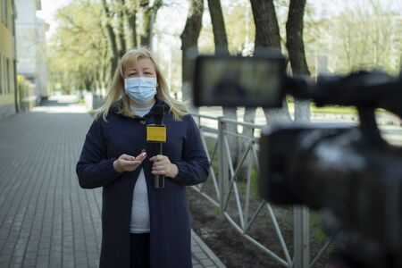 A female journalist in a protective medical mask is reporting in a deserted city.