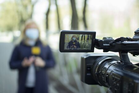A female journalist in a protective medical mask is reporting in a deserted city. Stockfoto - 147983603