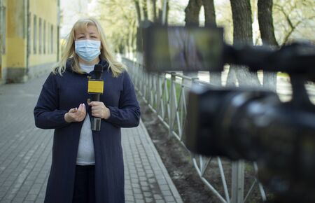 A female journalist in a protective medical mask is reporting in a deserted city. Stockfoto - 147983604