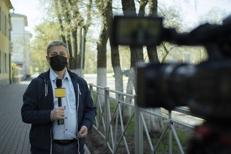 A middle- aged European journalist in a protective medical mask is reporting in a deserted city. Stockfoto - 147983605