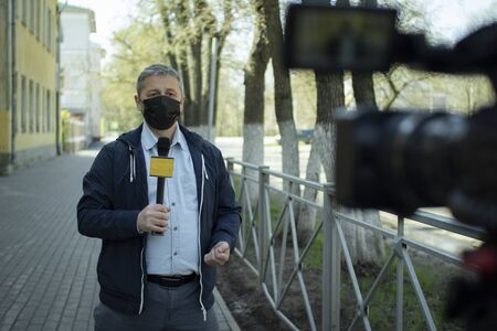 A middle- aged European journalist in a protective medical mask is reporting in a deserted city. Stockfoto - 147983606