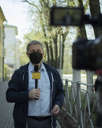 A middle- aged European journalist in a protective medical mask is reporting in a deserted city. Stockfoto - 147983608