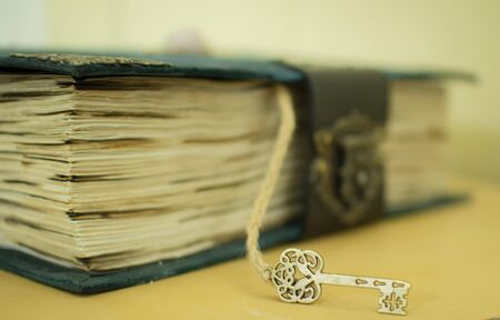 Vintage book with a key on a wooden background in classic blue color, as a concept of history