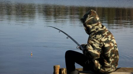 Fisherman in camouflage on the shore of the lake. Fishing with a float rod on the water. A teenager sitting on the riverbank and patiently fishing. Stockfoto - 147580762