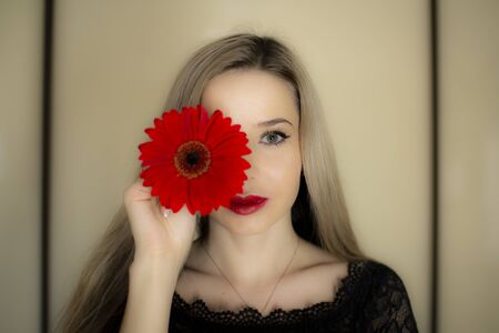 Portrait of a girl with a red gerbera flower. Stockfoto - 149418437