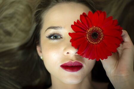 Portrait of a girl with a red gerbera flower. Stockfoto - 149512033