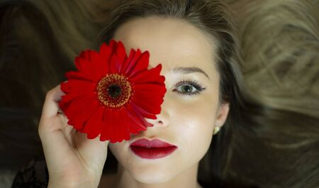 Portrait of a girl with a red gerbera flower. Stockfoto - 149504716