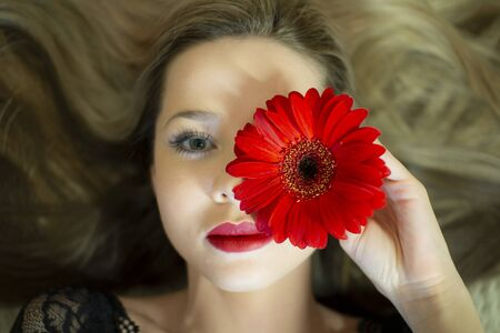 Portrait of a girl with a red gerbera flower. Stockfoto - 149511913