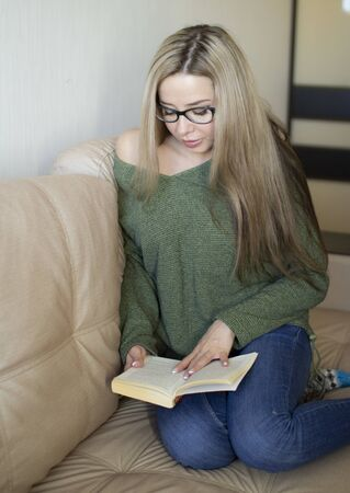 A pretty young woman is happy to read a book at home. Stockfoto - 149991689