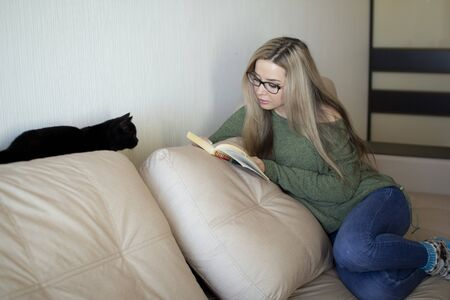 A pretty young woman is happy to read a book at home. The black kitten watches curiously. Stockfoto - 149991690
