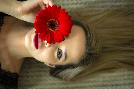 Portrait of a girl with a red gerbera flower