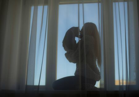 The silhouette of a girl with loose hair and a black kitten on the window Stockfoto - 150510502