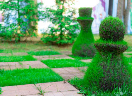 Chess pieces made from grass. Image of a street chess piece Archivio Fotografico
