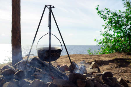 Pot on the fire by the lake. Camping with a pot over a burning fire. Stockfoto