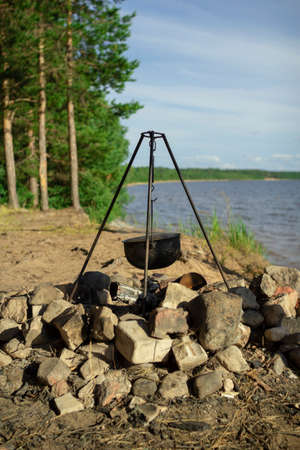 Pot on the fire by the lake. Camping with a pot over a burning fire. Stok Fotoğraf - 152066515