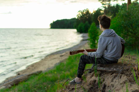 A teenager plays a guitar while sitting on the shore of a lake. Stockfoto