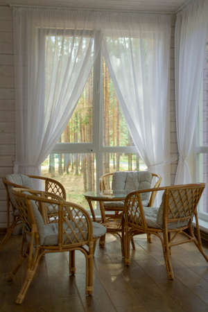 Rattan furniture on the summer porch. Outside the window is a pine forest