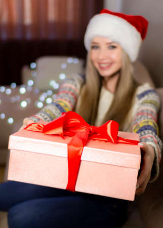 Beautiful blonde in a new years image with a gift box in her hands.