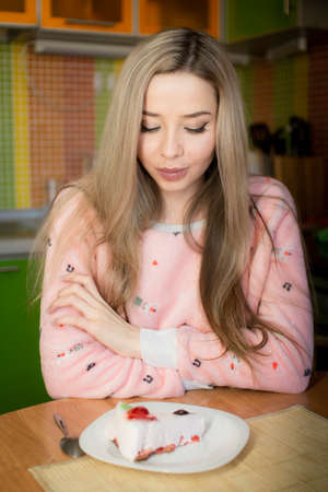 A beautiful girl is sitting in the kitchen in pink pajamas and looking at the cake. On a diet. Stockfoto