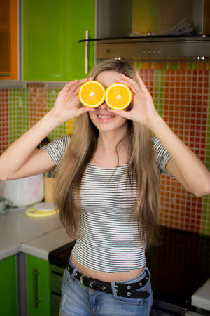 Portrait of a beautiful girl with orange slices in her hands .