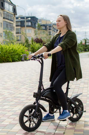 A young woman rides an electric Bicycle through the city.