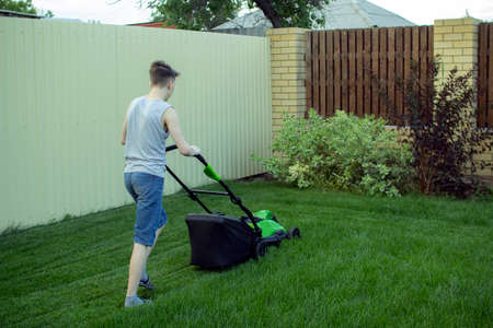 A teenager mows the lawn with a lawn mower. Imagens