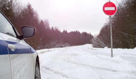 Car in front of a STOP sign on a winter forest road . The safety alert symbol.