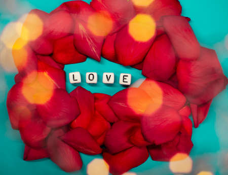 The word love on the background of rose petals . Valentines Day. Background concept of love and beauty Imagens