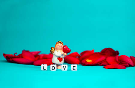 Charming angel and the word love on the background of rose petals .Valentines Day. Postcard for the holidays.