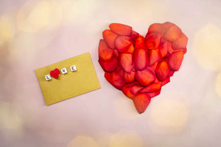 Heart of red rose petals on a pink background.