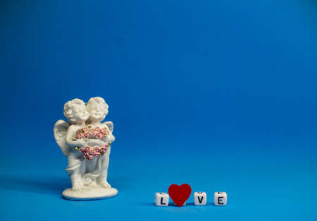 Two cute angels and the word love are made of ivory .Valentines Day. Postcard for the holidays.
