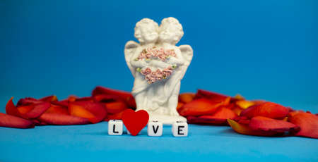 Two cute angels and the word love on the background of rose petals .Valentines Day. Postcard for the holidays