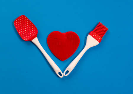 Silicone kitchen utensils with a red heart and a place for text. Kitchen banner for Valentines Day.