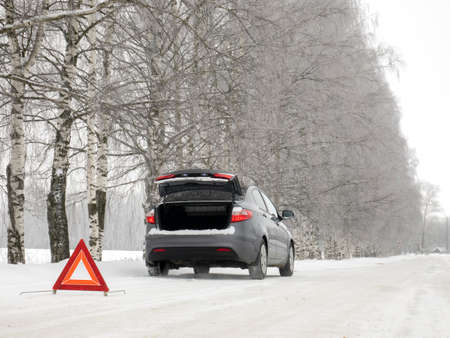 Emergency red sign on a snow-covered road.Car breakdown on the highway.