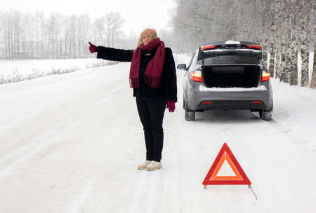 A woman tries to stop a car on a winter road. Sign on an emergency stop. Imagens
