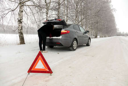 Car breakdown on the highway in winter. Sign on an emergency stop.