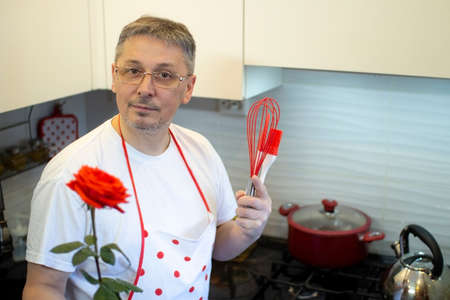 A man in an apron cooks in the kitchen and meets his girlfriend with a rose in her hands.
