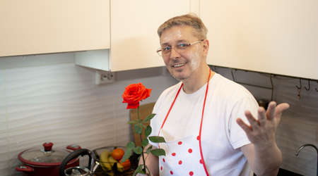 A man in an apron is cooking in the kitchen and meets his girlfriend, offering a rose . Imagens