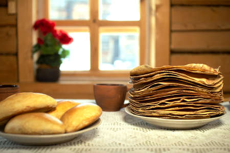 Pancakes in a wooden house on the background of a window. Imagens