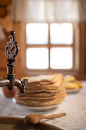 Samovar and pancakes in a wooden house on the background of the window.
