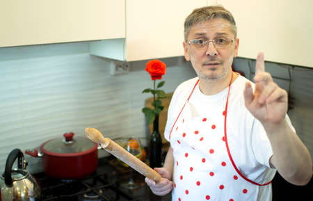 A man in an apron in the kitchen with a rolling pin in her hands.
