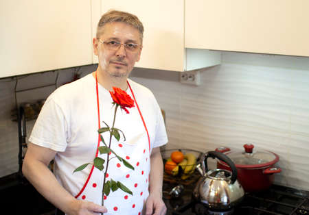 A man in an apron is cooking in the kitchen and meets his girlfriend, offering a rose . Stockfoto