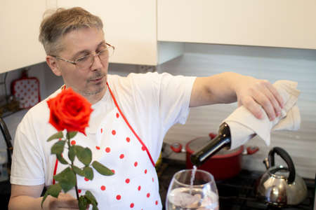 A man in an apron cooks in the kitchen and meets his girlfriend, offering a rose and wine.